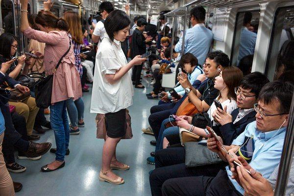 Люди в метро с телефонами